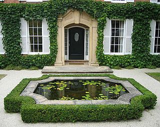 Love the boxwood bordered koi pond in front of the house.