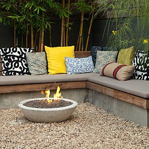 "A ready-to-roar gas firepit housed in a concrete ""wok"" from Potted heats the yard's main seating area. The cushy  pillows are covered in cloth from F & S Fabrics."