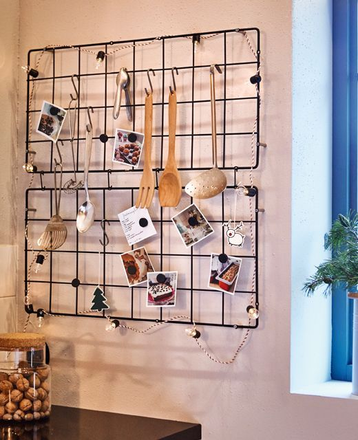 Two wire trellises hang on a kitchen wall, displaying cooking utensils, recipes and decorations.