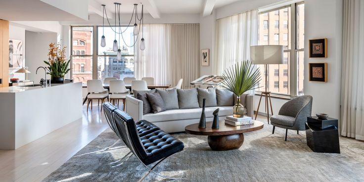 Apartamento de esquina com moveis clássicos, janelas grandes com bastante iluminação natural, ambientes integrados e tapetes monocromáticos. O apartamento é bem leve, clean e minimalista.