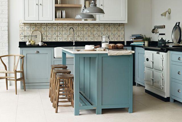 Une cuisine de campagne dans les bleus Lumineuse, cette cuisine joue avec différents tons de bleus pour rester actuelle. Les codes traditionnels rustiques, le fourneau à l'anglaise et la crédence à carreaux de ciment sont réactualisés par le bleu des meubles. Le bar central qui fait aussi espace repas invite à la convivialité . L'idée déco en plus : les tabourets et le siège en bois brut qui réchauffent les bleus .   Cuisine Vermont,façades en chêne, prix sur devis, Grange.
