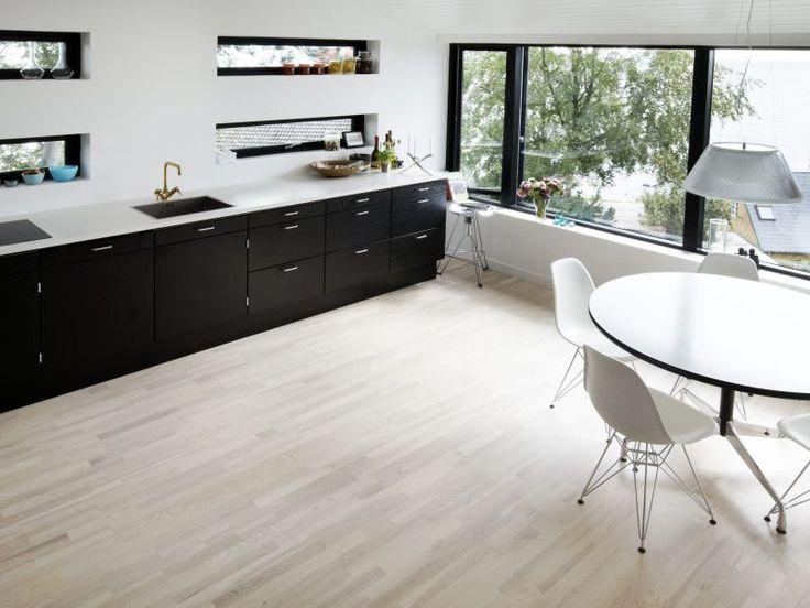 White timber floors + Black kitchen.