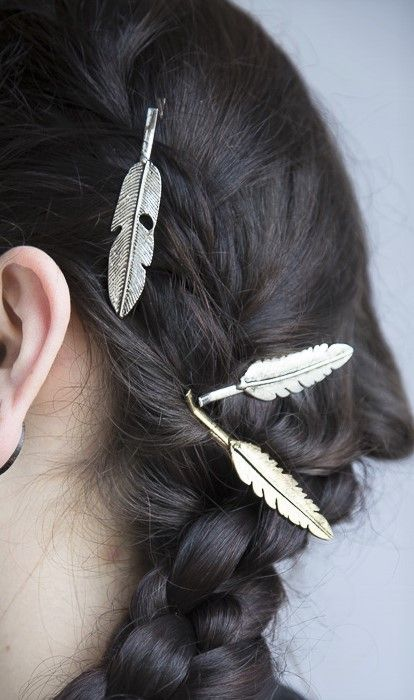 A set of four feather hair clips is fastened to a card. Alternating tones of silver and gold allow the wearer to choose their look based on their mood, or switch them up for a mixed metal look. Handcrafted in India.