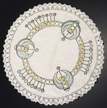 """Arts & Crafts round table mat, H. E. Verran Company Inc., Royal Society, unknown number, ca.1911-1912, green, blue, yellow, ochre and black floss with green stenciling on off white linen fabric, lace border, satin, outline and long and short stitches, 21""""dia., pictured in Style 1900, Summer/Fall, 1999  