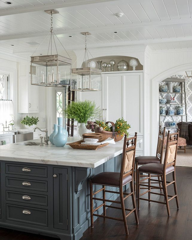 """Traditional Shingle Home with Blue and White Interiors Kitchen Island Paint Color: Farrow and Ball Down Pipe No.26  A pair of the """"Urban Electric Co Chisholm Lights"""" are suspended from a white beadboard clad ceiling."""