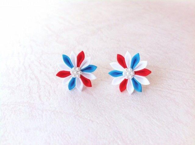 人気のひな菊デザインのピアスに、新しいお色が登場です。  ポップな赤×青×白の配色は、「蘇芳色」と「縹色」を組み合わせた「葡萄染め」のかさね色目のイメージで、季節を問わず華やかに。  定番のマリンカラー・トリコロールのイメージも。  和風なお着物にも、洋風にカジュアルなお洋服にも合わせていただける、万能カラーになりました。  重さはコットンパール程度。 吹けば飛ぶほどの軽さです。  オフィスやデートなどの普段づかいはもちろん、結婚式やパーティーのドレスや浴衣、成人式の着物など長時間着用するシーンでも、とっても楽ちんですよ!  パール調の、白いお箱にいれてお届けします。   「つまみ細工」は、小さな正方形の生地を、ピンセットを使って一枚一枚ていねいに折りたたみ、糊付けしてつくる、日本の伝統工芸です。  ピアスに使用している生地の大きさは、わずか1cm四方。  ちいさな花びらやパーツをひとつずつ配置して、手作業でおつくりしています。  繊細な手仕事の一品をお手元にどうぞ。    素材:キュプラ 金具:ゴールドメッキ ※イヤリングへも変更可能です 寸法:お花の直径約1.5cm…
