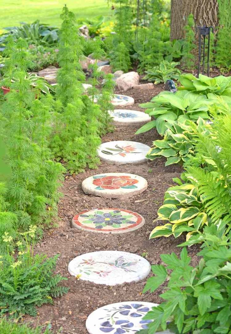allée de jardin en pas japonais ornés de dessins colorés, plantes vertes et arbres