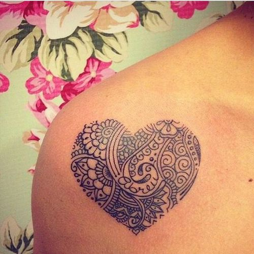 This is heart - shaped tattoo on shoulder. Tattoo has no outlines, but has many ornaments inside. You can see various types of details - floral details, lines, circles, dots.