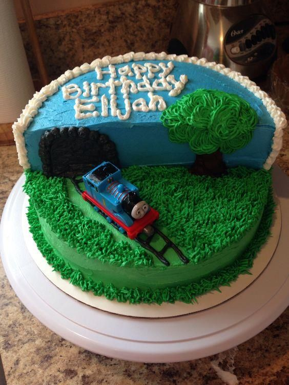 Tunnel Cake  The trick to this tunnel cake? The second layer is cut in half and stacked on one side to create a tunnel. Green and blue icing add landscape decor before Thomas completes the look.  #thomasandfriends #thomasbirthday #birthdaycakes #thomasthetrain