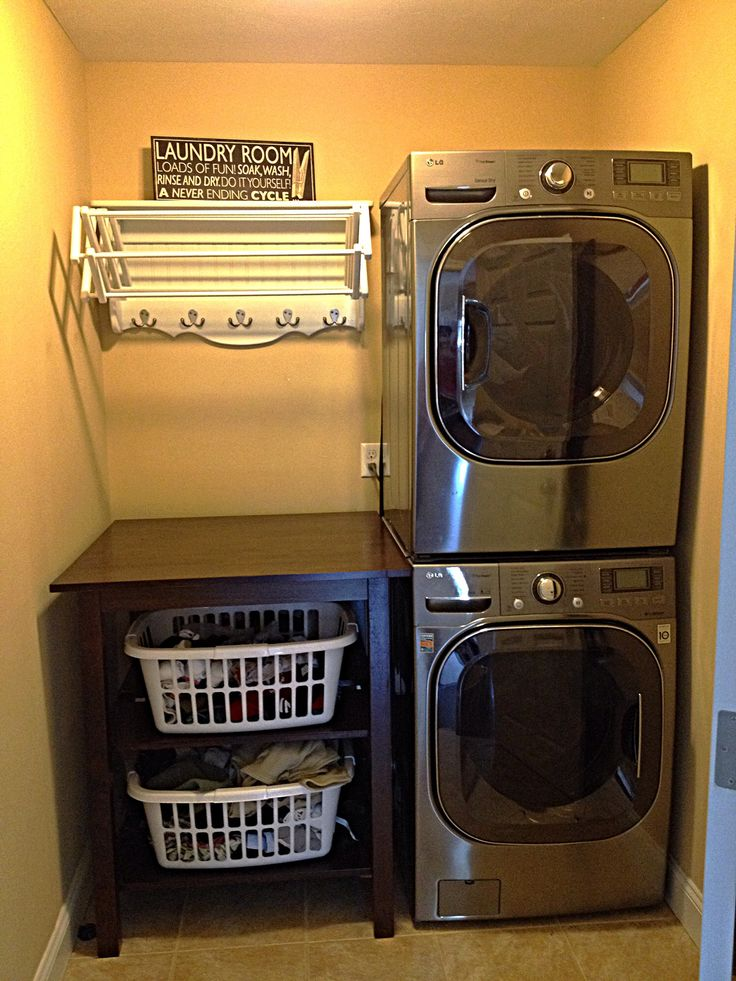 Finished Laundry room, washer/dryer stacked to create room for folding table/basket storage. Standard pub table converted to laundry station by adding four shelves (two front hinge), table holds four standard baskets, two each shelf.