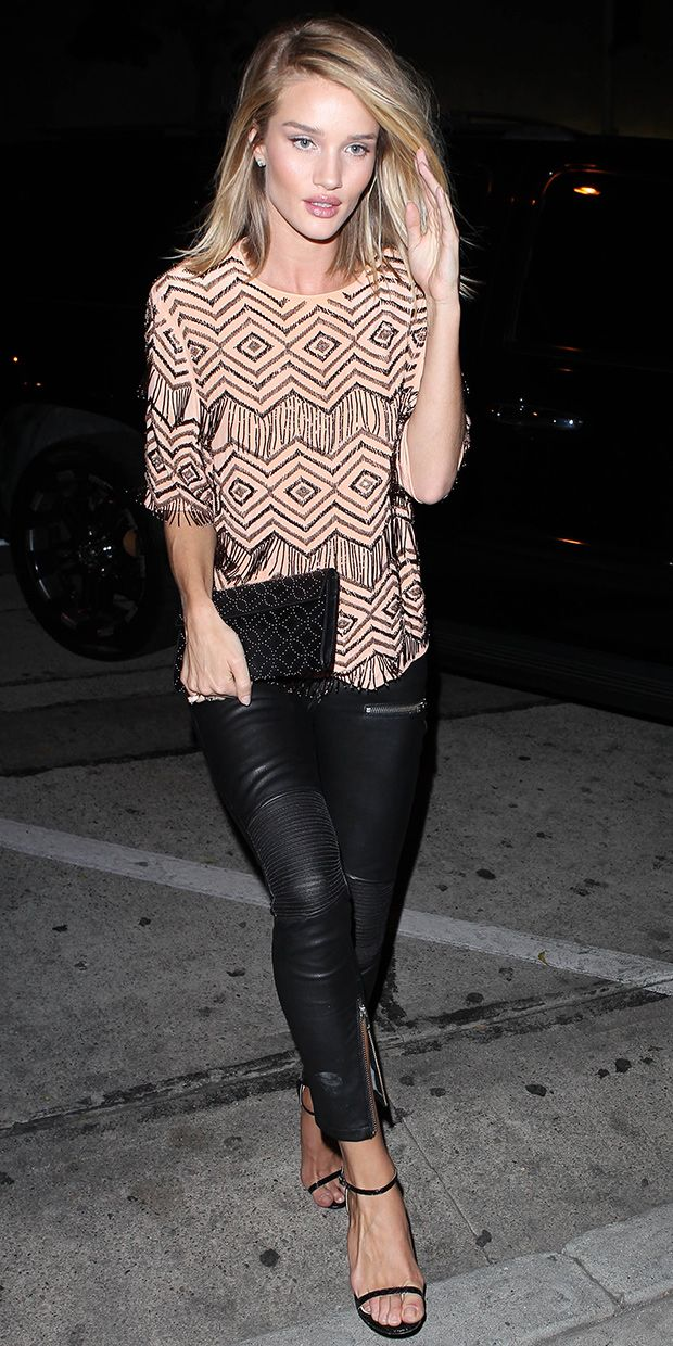 Rosie Huntington-Whiteley in a beaded top, leather pants with zips, and black ankle strap heels