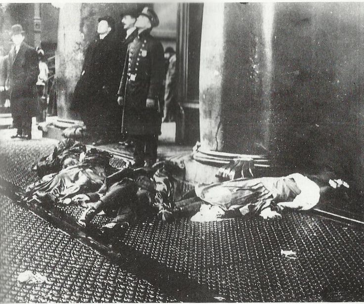 Policemen stare up as the Triangle fire of 1911 rages, while the bodies of factory workers who plunged to their deaths to escape the blaze lie on the sidewalk..this fire and the exposed working conditions of these girls (which ultimately led to their deaths) lead to OSHA and to safer working conditions in the US.