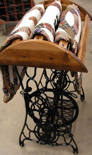 Antique sewing machine base turned quilt rack  Love it!  I have one as a display case for family momentos, one is now a laundry folding table and 3rd is a sofa table to display photos.  Not that I'm obcessive, but I like this idea too!