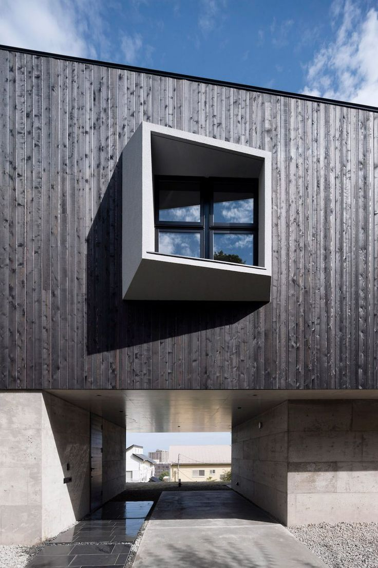 An Angular, Blackened Wood Structure Sits Atop Two Concrete Blocks To Form  This House In