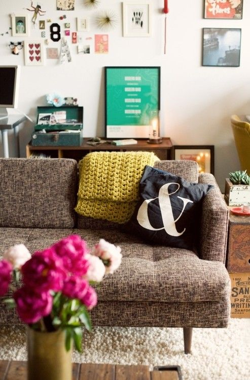such a cute and quirky living room, i love that sofa, the rug, and the amazing bits and bobs on the wall