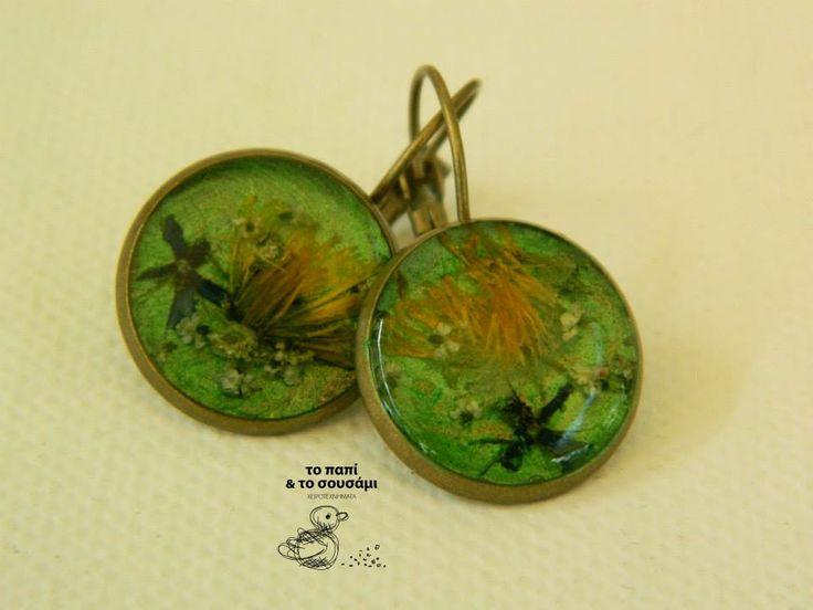 Στρογγυλά μπρούτζινα κρεμαστά σκουλαρίκια με μικροσκοπικά αληθινά λουλούδια,μαζεμένα με προσοχή, σε πράσινο φόντο. Round bronze resin earrings with natural tiny flowers collected with care on a green background.