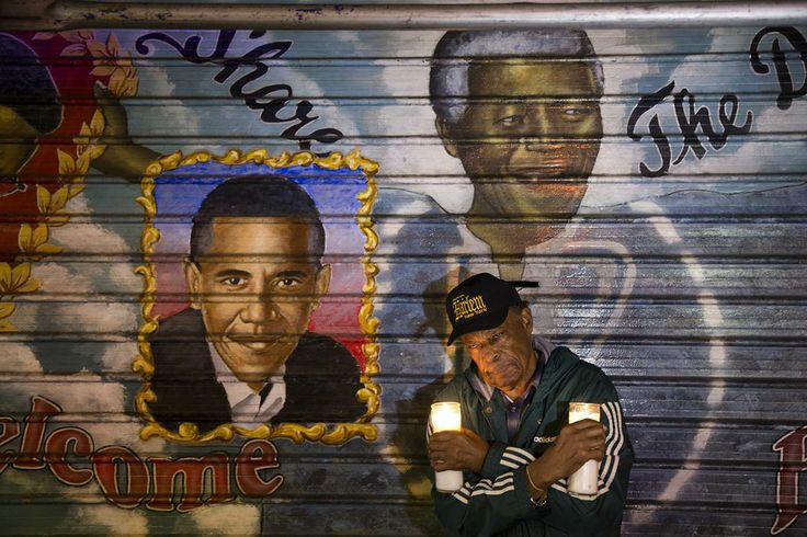 """An artist who goes by the name """"Franco the Great"""" stands in front of a mural of Nelson Mandela, on December 6, 2013.  He painted in 1995, on 125th Street in the Harlem neighborhood of New York. U.S. President Barack Obama was added to the mural at a later date."""