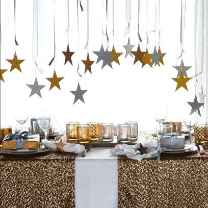 Gold and silver stars hanging. Jazz up your New Year's Eve table. Visit www.redonline.co.uk for more festive ideas.