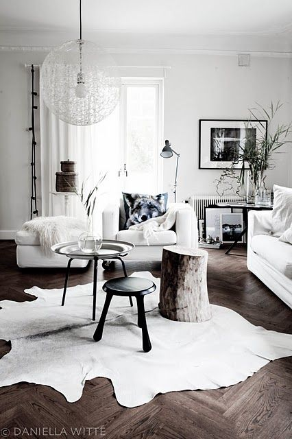 Living room rug  -   Daniella Witte - Chaos pendant light, tree stump side table, tray table, leather rug, mohair throw, white ottoman, white armchair, white couch, dark herringbone flooring