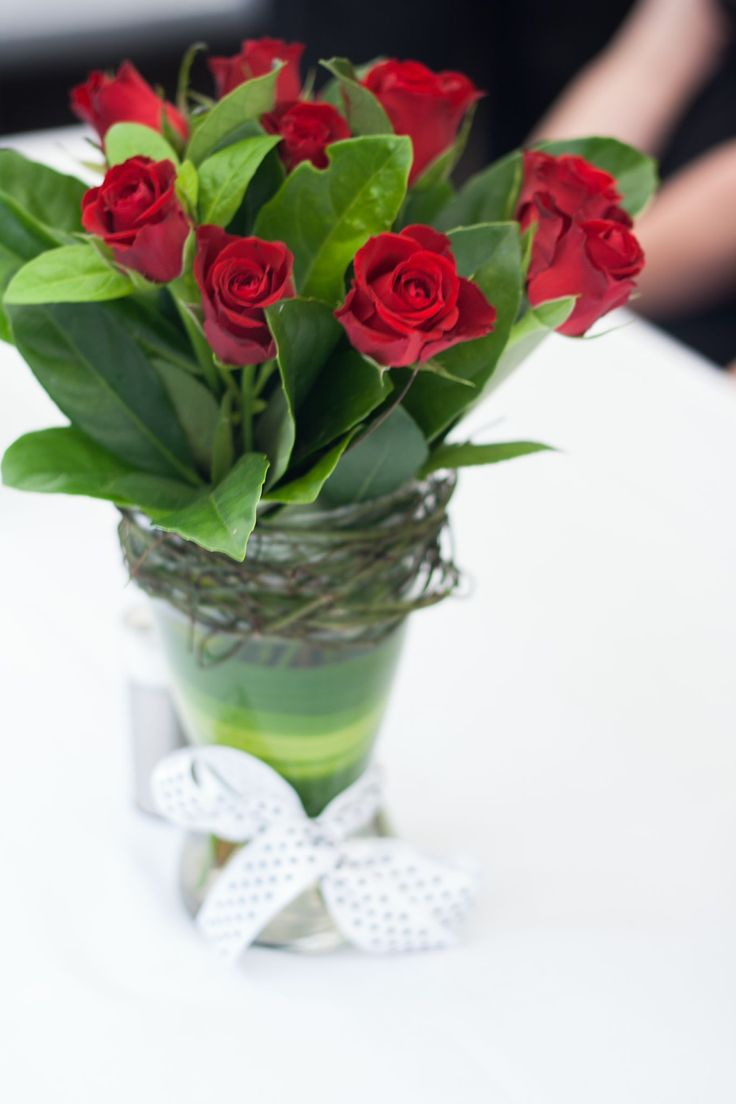 Red roses for a wedding reception. Including vine and ribbon detail.