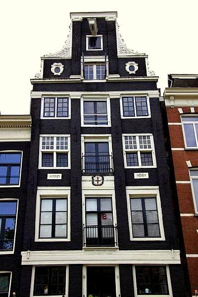 Amsterdam - Amstel 14 - koopmanshuis 1661, vier Dorische pilasters over twee verdiepingen, in hals Ionische pilasters, bloemmotief in en langs klauwstukken, twee oeils-de-boeuf's, gevelsteen met wapen van Londen, jaartalsteen, top beschadigd (geen fronton meer).