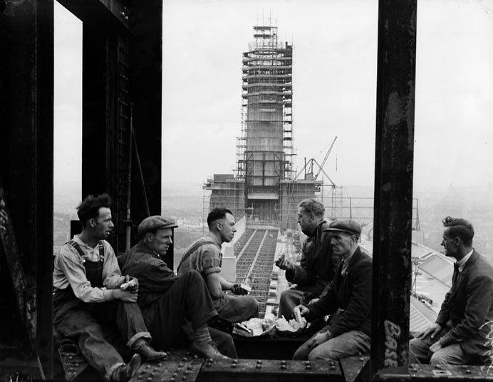 1932: Construction workers take a lunch break with one of the two 300ft high chimneys of Battersea Power station, which was nearing completion, in the background