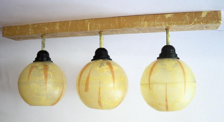 Abbiamo utilizzato forme e colori che possano valorizzare al massimo questo lampadario. La base in legno è stata rivestita in carta di riso e dipinta nei colori dell'ocra. Al di sotto, le tre sfere che racchiudono la luce sono in materiale plastico di recupero, la loro apertura consente di ottenere una gradevole illuminazione e anche di sostituire in maniera agevole le lampadine.