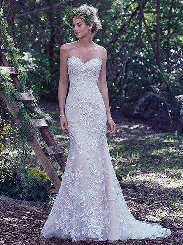Maggie Sottero - TRENA, Floral appliqués sparkle throughout this classic lace fit and flare wedding dress. Three dimensional flowers adorned with Swarovski crystals add texture and femininity to the skirt. Finished with a soft sweetheart neckline and corset closure.