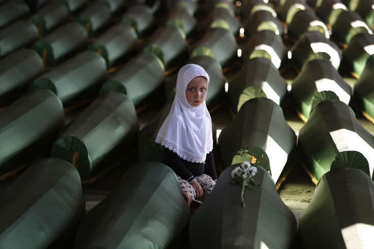 Ema Hasanovic, 5, a young Bosnian Muslim girl, pays her respects near to the coffin of her uncle, in the Memorial center in Potocari, on July 9, 2014. Hundreds of people turned out to pay their respects to 175 victims of the Srebrenica massacre. The remains of the men and boys, found in mass graves and identified through DNA analysis, were buried in Srebrenica during the 19th anniversary of the massacre. #  Amel Emric / AP