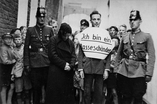 "The Protection Police, Schutzpolizei, caught the Jew Julius Wolff and his Aryan girlfriend Christine Neemann for public humiliation because of Rassenschande (race defilement), Norden, 22 July 1935. The sign reads ~ ""I am a defiler of the race"". The Schutzpolizei was a branch of the Ordnungspolizei-ORPO, responsible for regular police duties within municipal cities and townships. In Jan 1934 the NSDAP reorganize all police authorities under direct Reich control.  Heinrich Himmler was…"