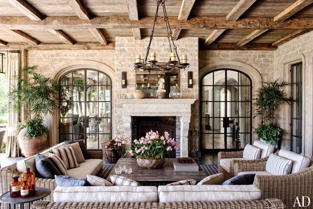 A loggia features a chandelier and sconces by Gregorius | Pineo and RH wicker sofas and chairs cushioned in a Clarence House fabric; the reclaimed-oak ceiling beams and antique limestone mantel are from Koen Van Loo of