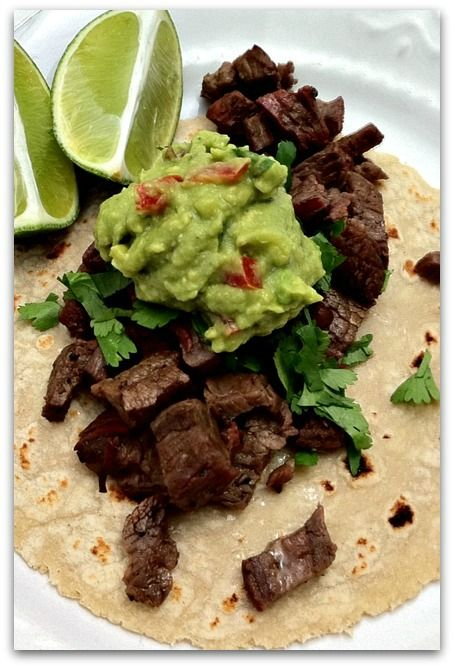 Carne Asada Ingredients: freshly chopped cilantro, about 1/2 cup 1/4 cup red wine vinegar the juice of 4 limes 2 Tbs vegetable oil 1 Tbs kosher salt 1 Tbs freshly ground black pepper 1-2 tsp sugar 1 white onion, thinly sliced 2 Lbs flank steak  Garnish Ingredients: Plenty of freshly chopped cilantro 1 white onion, finely chopped several limes, cut into wedges Guacamole