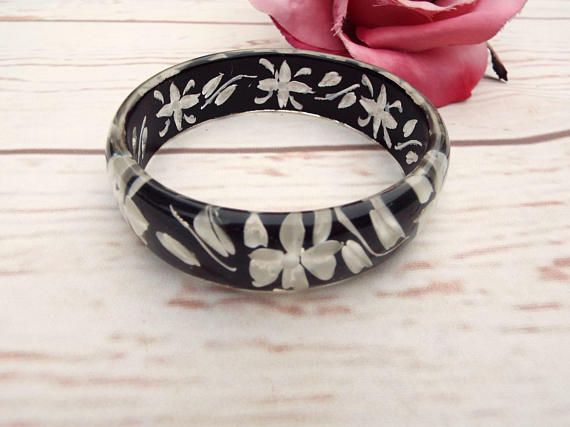 Here we have a beautiful original vintage carved bangle  The vintage bangle is a reversed carved style which is mainly black with the rose carvings painted white  It has been hand carved and the inside has a textured finish - please enlarge photos to see the intricate work around the