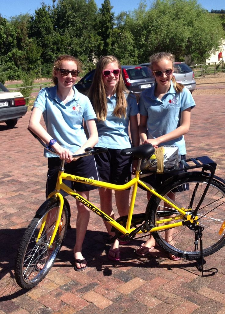 Three proud fundraisers from the Thomas Clapham School in London pose with one of the 20 bicycles they donated to school children in South Africa.