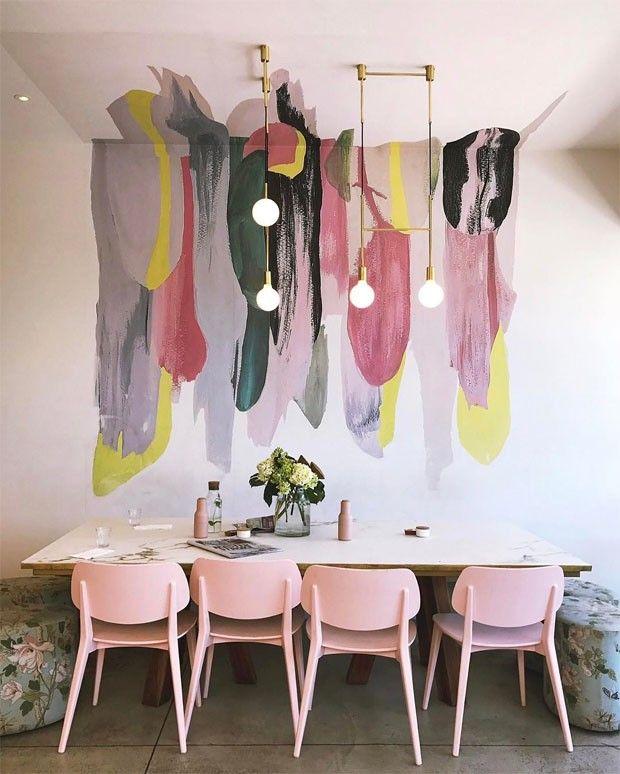 """""""Nesta sala de jantar – que na verdade é uma mesa comunal – do café australiano Mister Hoffman, as cores têm um papel preponderante. A paleta de candy colors é responsável por tornar rosa as cadeiras – em um tom que têm sido chamado de millennial pink – assim como as flores que estampam os bancos nas extremidades."""" (Foto: reprodução)"""