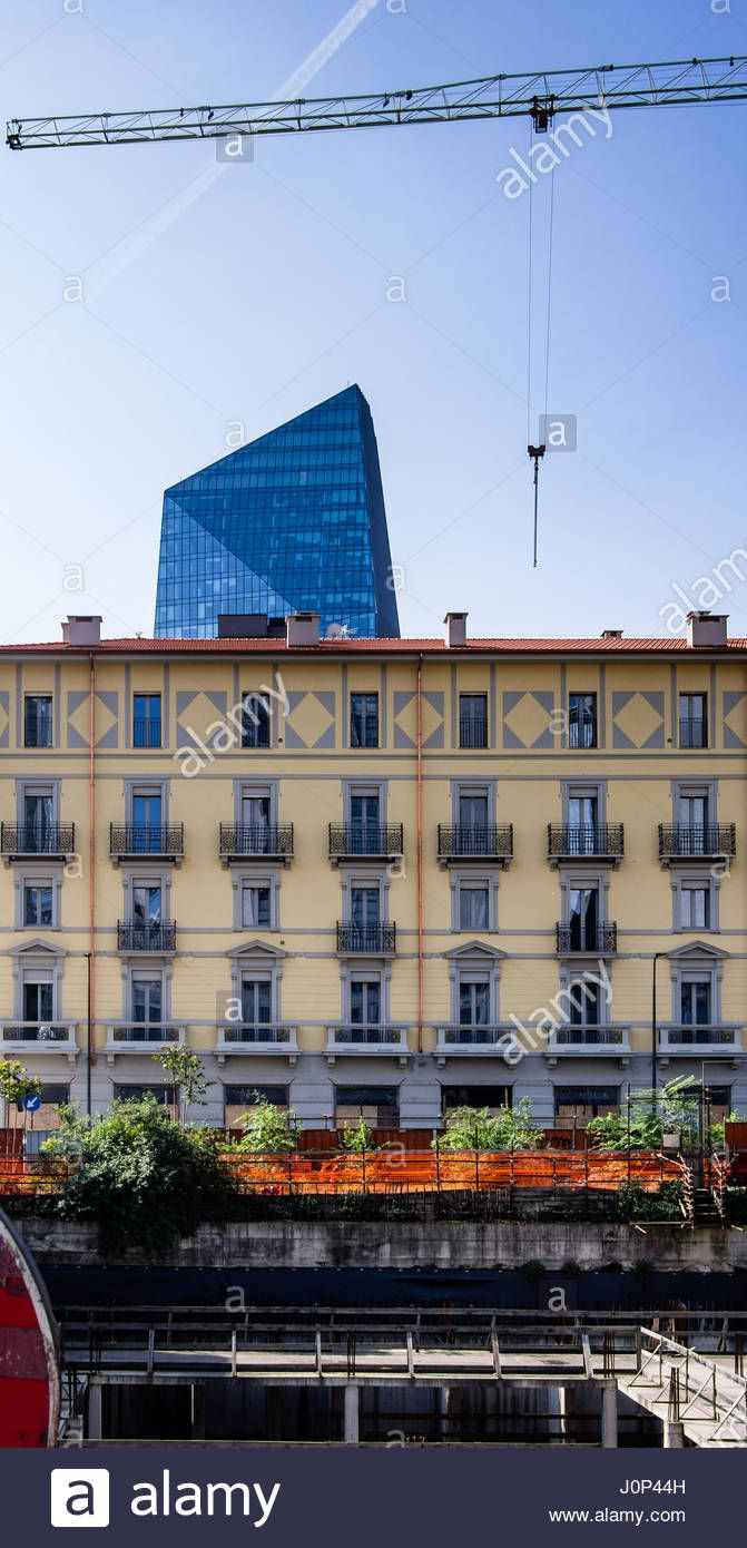 Download this stock image: Architecture contrast in Milan, Porta Nuova district, between Torre Diamante skyscaper and old traditional popular housing of different periods. - J0P44H from Alamy's library of millions of high resolution stock photos, illustrations and vectors.