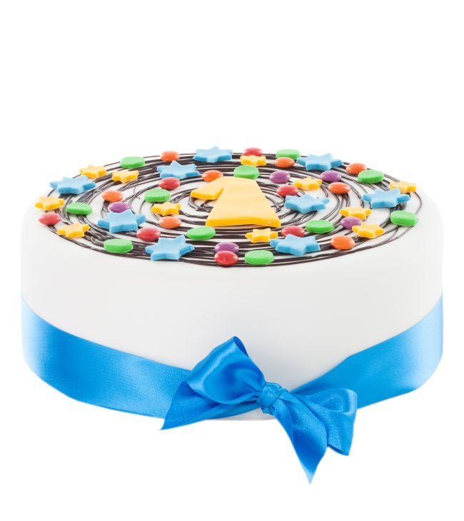 Dětský dort č.4 Dětský dort obalovaný fondánem, dozdobený čokoládou, kytičkami z fondánu, stuhou, lentilkami a číslicí.