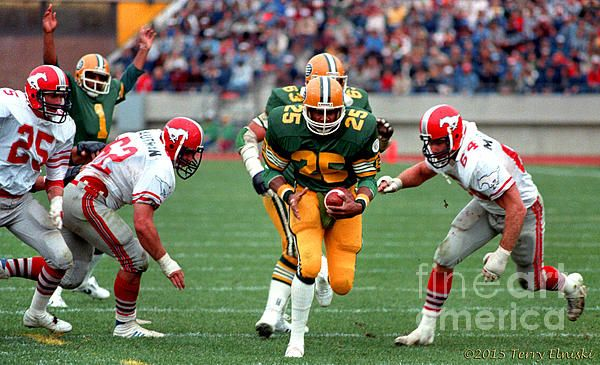 Photograph of Edmonton Eskimos running back Jim Germany #25 going into the endzone for a touchdown with QB Warren Moon #1 raising is arms in the background. Against the Calgary Stampeders, 1982.
