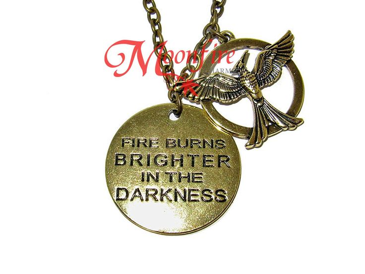 """""""Fire burns brighter in the darkness."""" - Katniss Everdeen This necklace features the quote by Katniss stamped on a token, accompanied by a Mockingjay charm. The bronze plated pendant measures 3 cm in"""