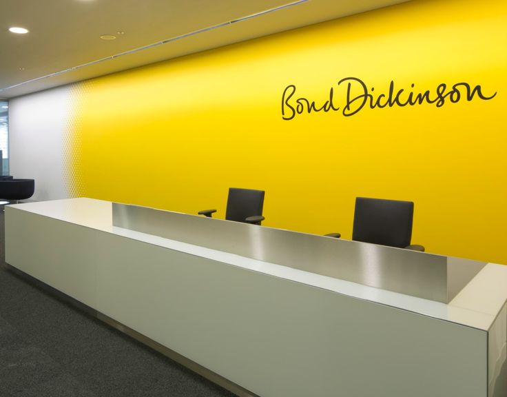This simple but elegant white reception desk with brushed chrome effect detailing provides a sophisticated welcome at this office reception area. The space uses a bright yellow wall and company logo to brand the area.