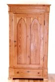 English Pine Single-Door Wardrobe  Beautiful English pine single door wardrobe or armoire, depending on how you use it. In honey pine with natural wood finish. Unusual small size allows for use in a limited space. Details include cathedral arch detail of door, dowelling for hangers, antique key and lock for door, and a single drawer at bottom. Can easily be converted to shelves. Perfect as an extra closet in a cottage or craftsman style décor.   $675