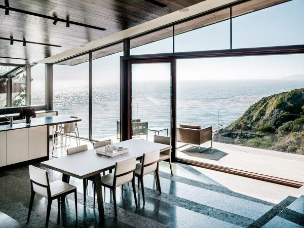 floor-to-ceiling windows frame sections of the picturesque ocean and landscape