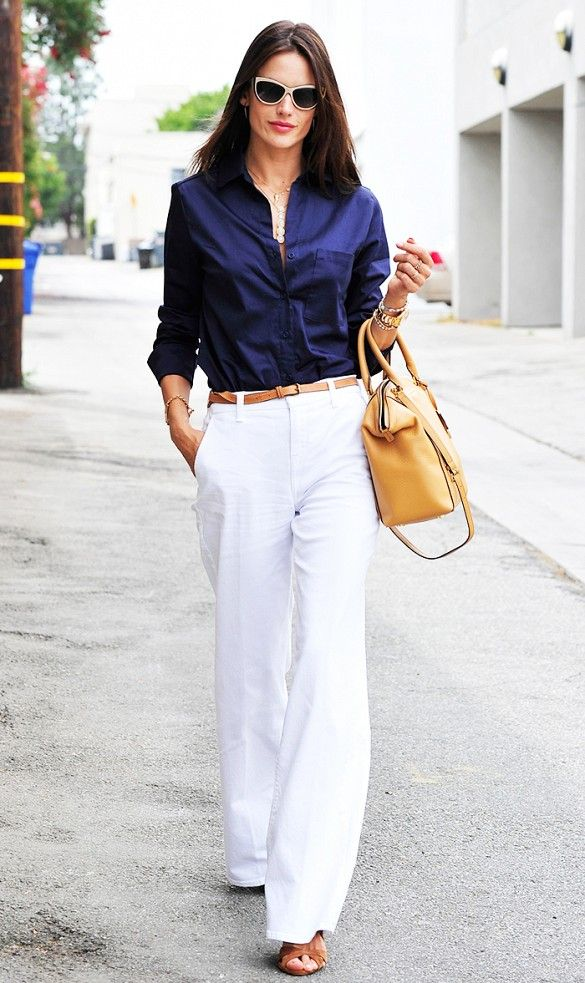 Alessandra Ambrosio wore white wide-leg pants, blue button-up shirt, and brown accessories- sandals, bag and belt.