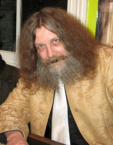 """His hair…  """"Alan Moore (born 18 November 1953) is an English writer primarily known for his work in comic books, a medium where he has produced series including Watchmen, V for Vendetta, and From Hell. Frequently described as the best graphic novel writer in history, he has also been described as """"one of the most important British writers of the last fifty years"""". He has occasionally used such pseudonyms as Curt Vile, Jill de Ray, and Translucia Baboon."""""""
