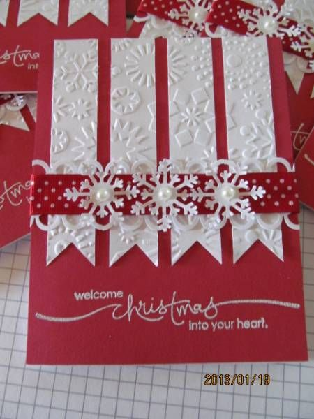 Lovely snowflake embossed white banners on red cardstock are a background for die-cut snowflakes and pearls.  Add a white-dotted ribbon and embossed sentiment for a handmade Christmas card.