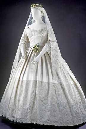 Wedding dress, England, 1865. Silk-satin dress trimmed with Honiton appliqué lace, machine-net and bobbin lace. Worn at the wedding of Eliza Penelope Clay and Joseph Bright, St James's Church, Piccadilly, London, 16 February 1865.