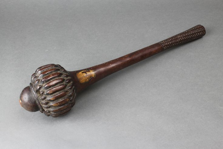 """Lot 214, A good 18th/19th Century I-ula-drisla Fijian throwing club with 2 (ex 6) inlaid mounts, the handle with geometric decoration, 16"""" long, with old collection label, est £500-800"""
