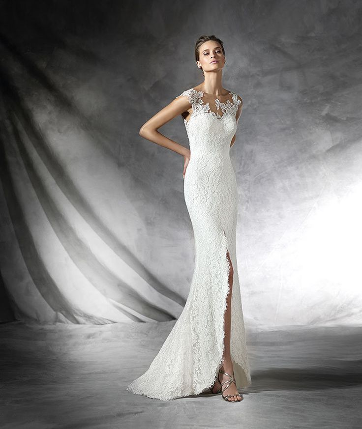 PRETA- Lace wedding dress with sheer underbodice decorated with lace appliqués. Skirt with front slit. Plunging V-back.