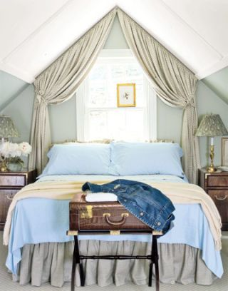"The guest cottage's snug bedroom is tucked under the sloping roof of the top floor. Waverly draperies frame the window over the bed, creating a cocoonlike effect. ""Instead of trying to brighten up a shady room, I chose dove gray walls to make it feel warm and inviting,"" explains Millena."
