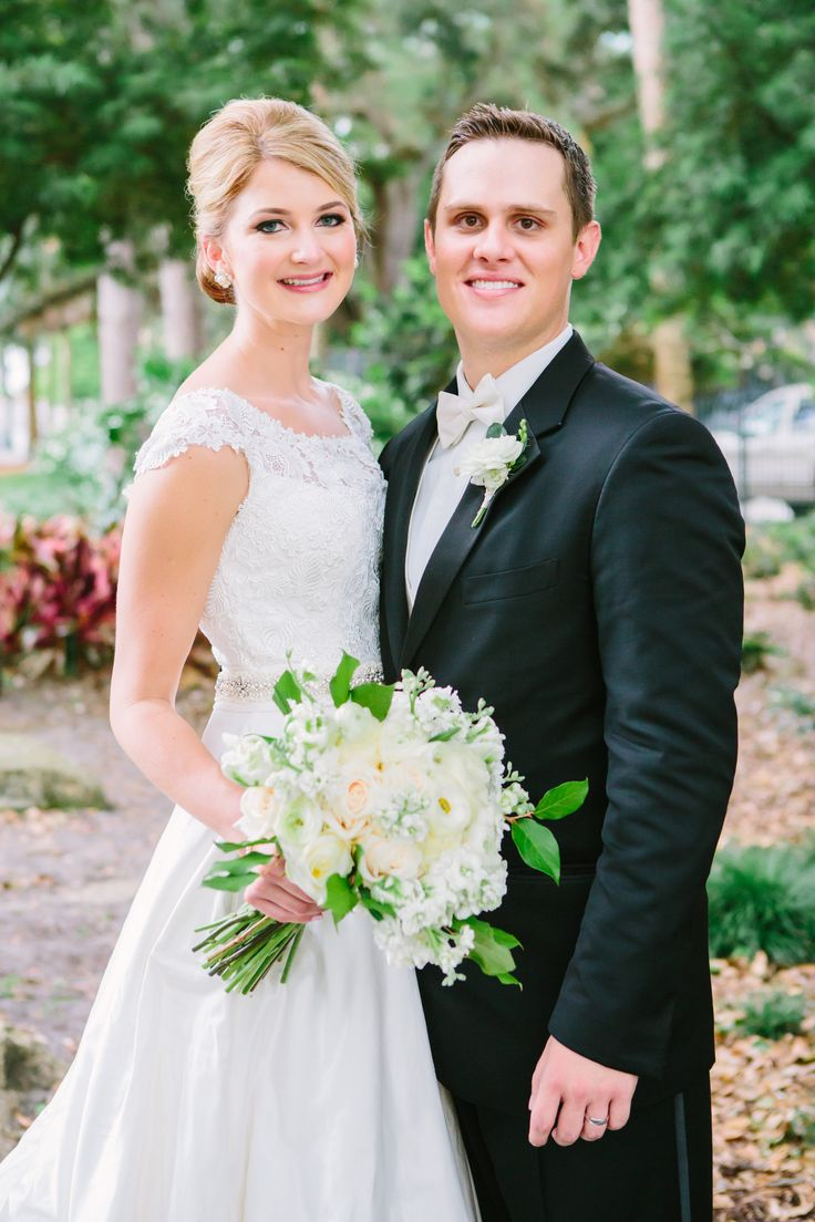 the bride holds her classic bouquet of white roses, champagne roses, white stock, white ranunculus and green parrot tulips. the groom in a black tux wears his boutonniere of white ranunculus.